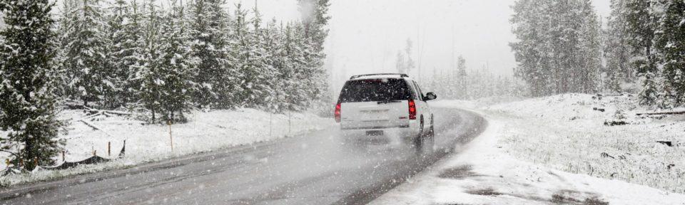 Hvit bil på vei i snølandskap