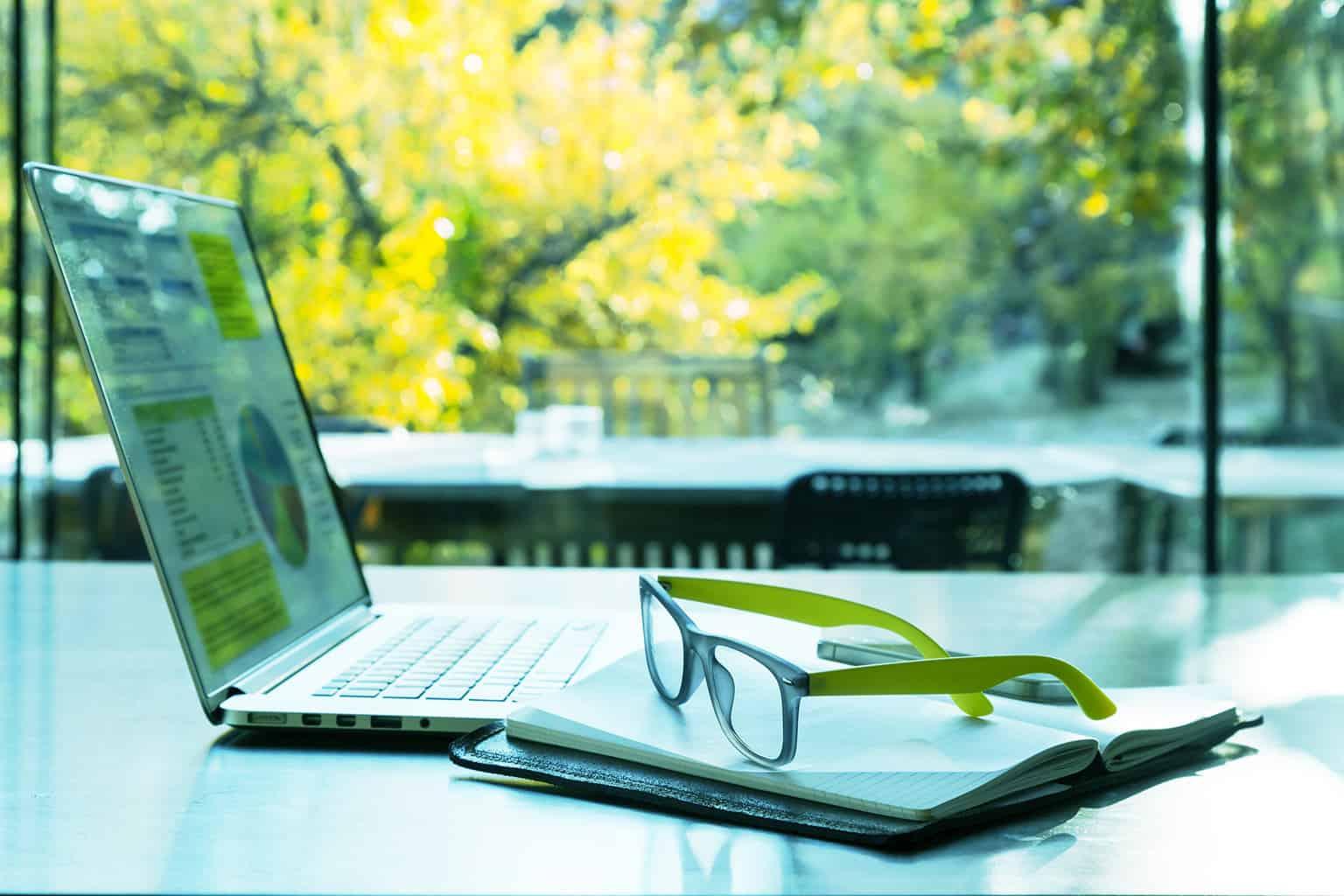 Laptop og briller som ligger på et verandabord med grønne trær i bakgrunnen